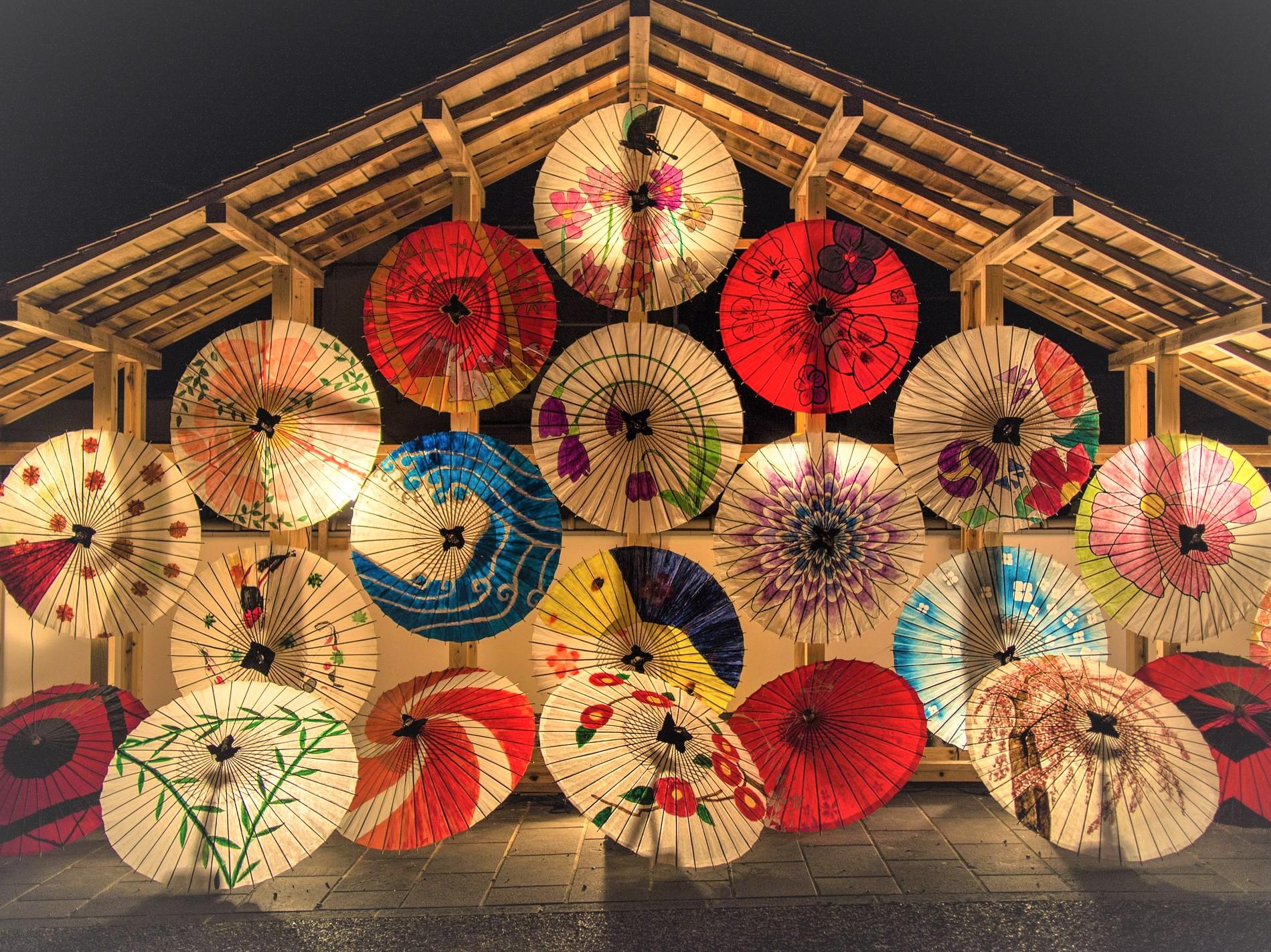 様々な絵柄や赤白青など色とりどりの和傘がピラミッドのように重なりライトアップされている幻想的な写真