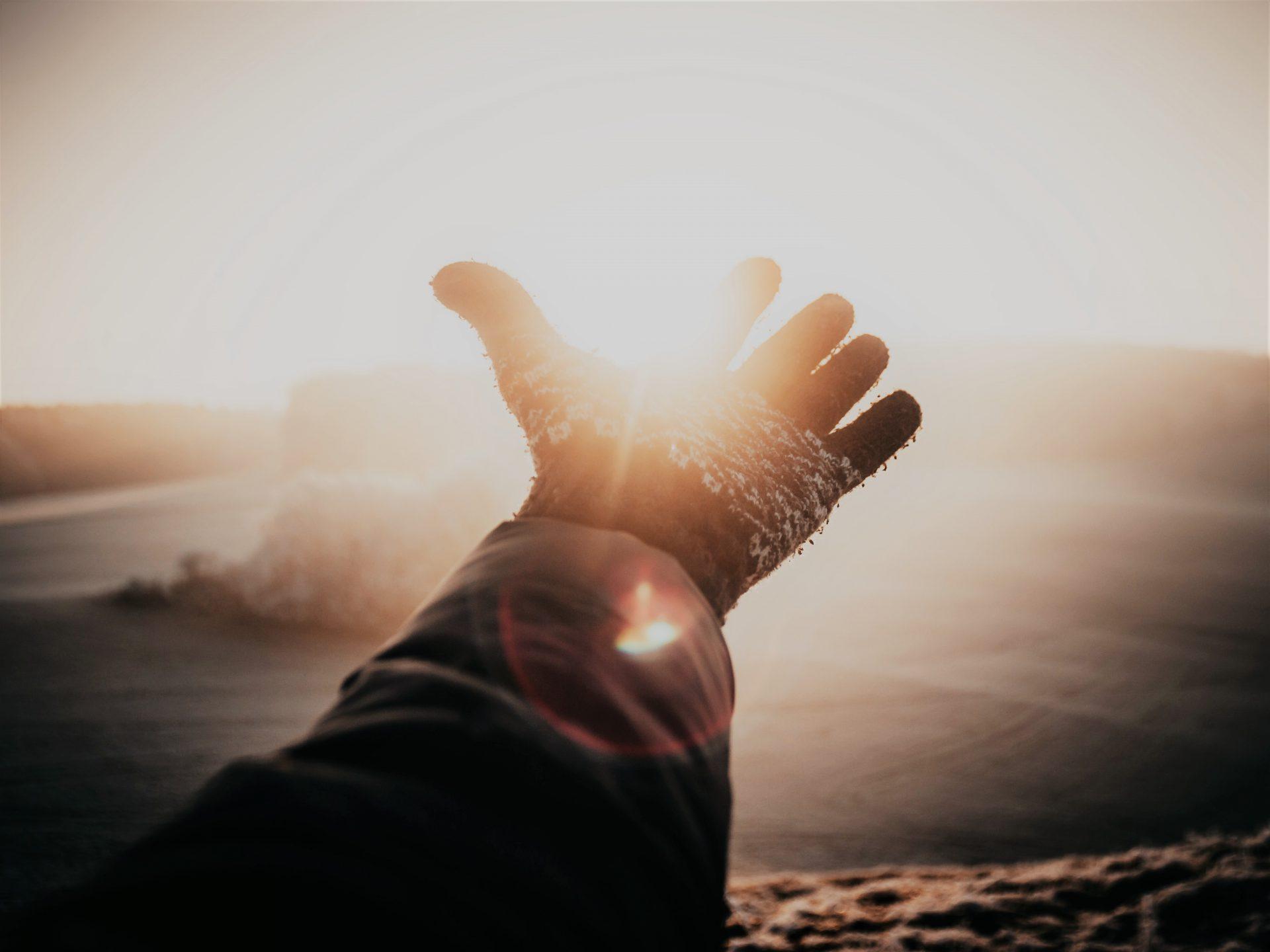 光に手を差し出している。手袋を付けた片手。