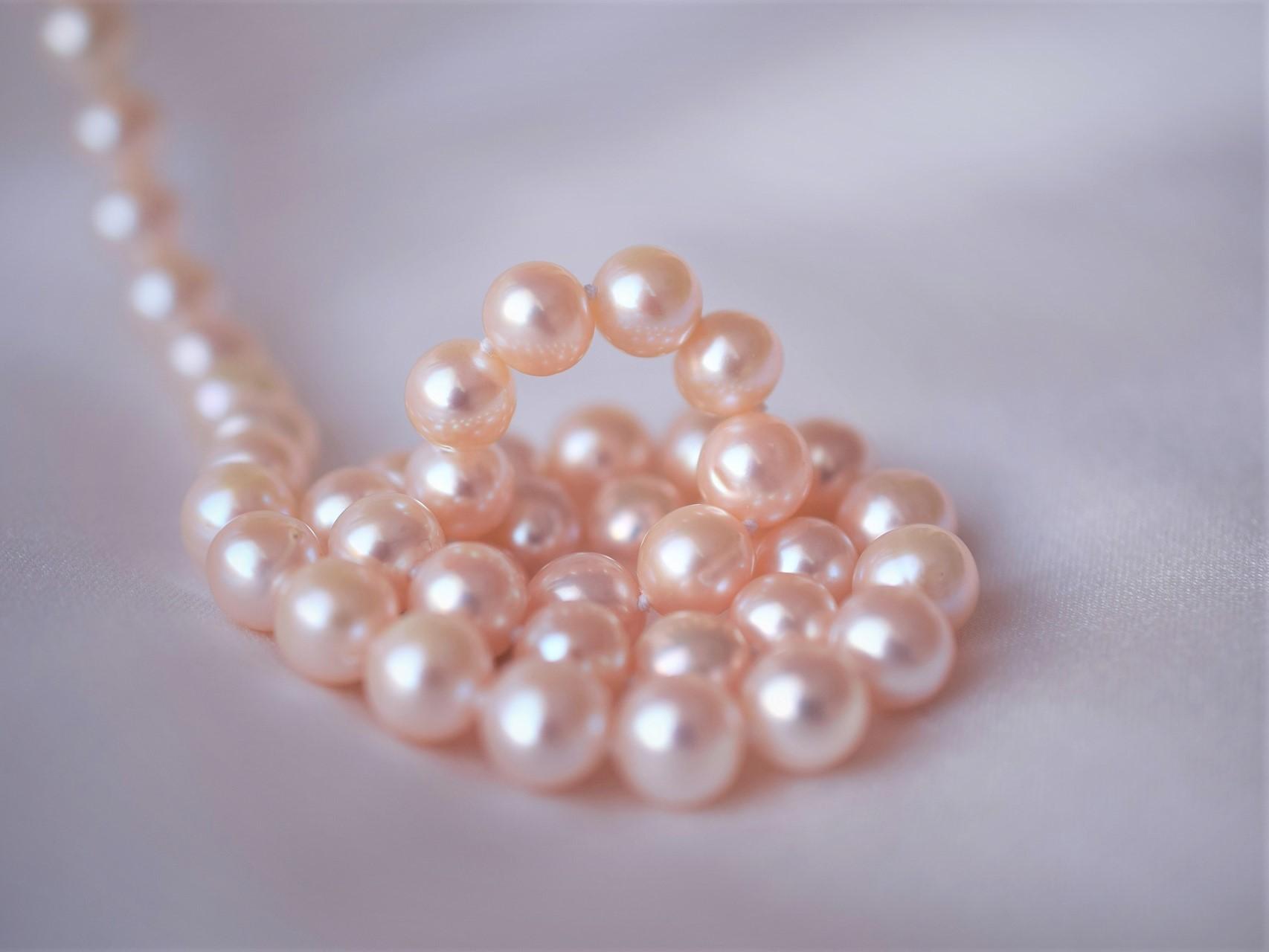 白いシーツの上にピンク色の輝く真珠が巻かれている