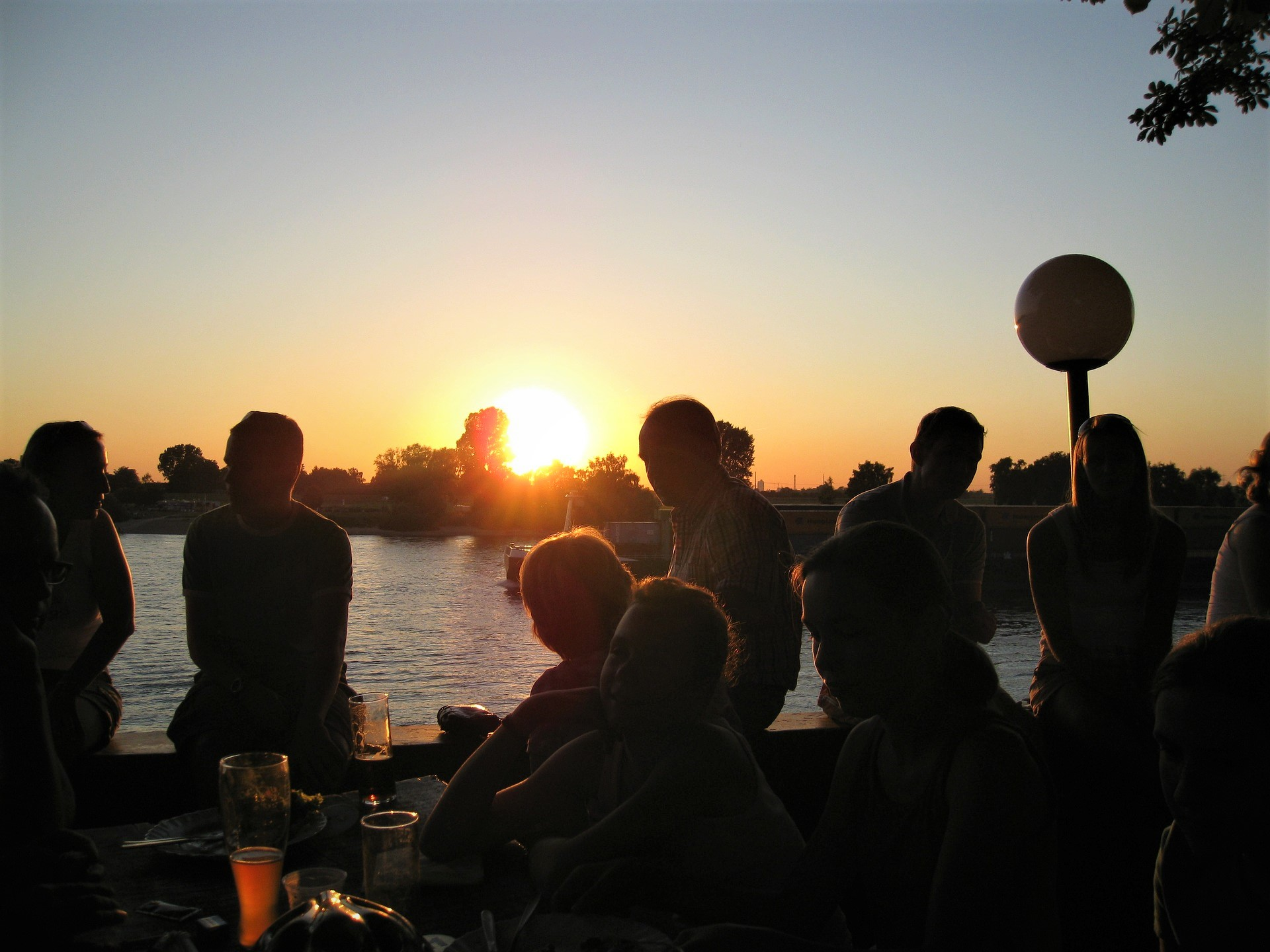夕日を見つめながらお酒を片手に楽しく語らう人々