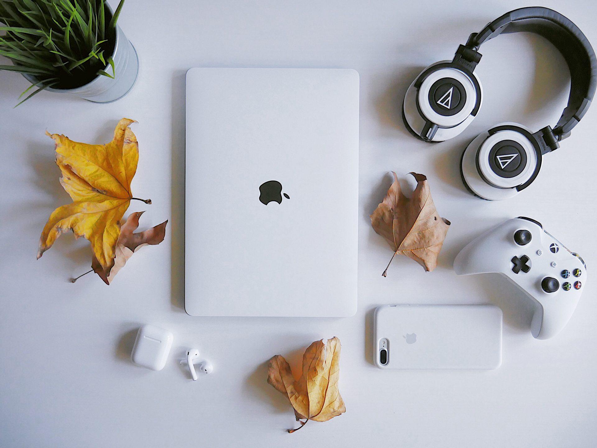 白いテーブルの上に並べられたヘッドフォンやパソコン、スマホの画像
