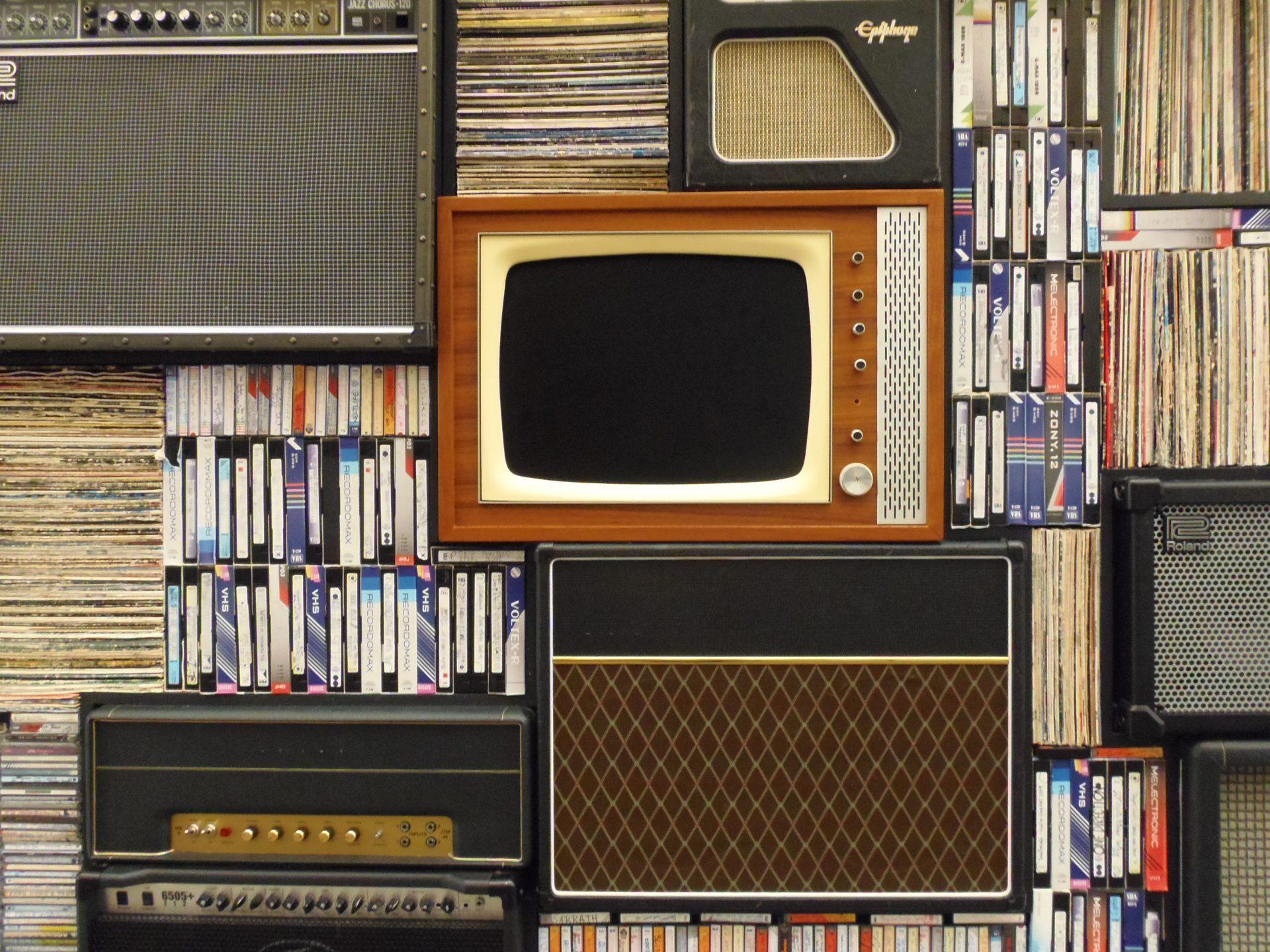 レコードとスピーカーの山に埋もれる古いブラウン管テレビの写真