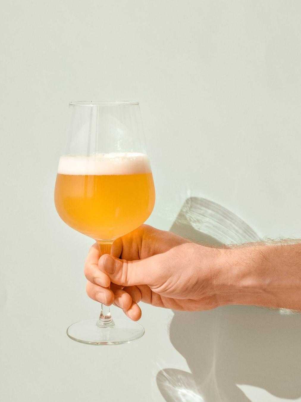 白い壁にグラスに入ったビールが注がれている