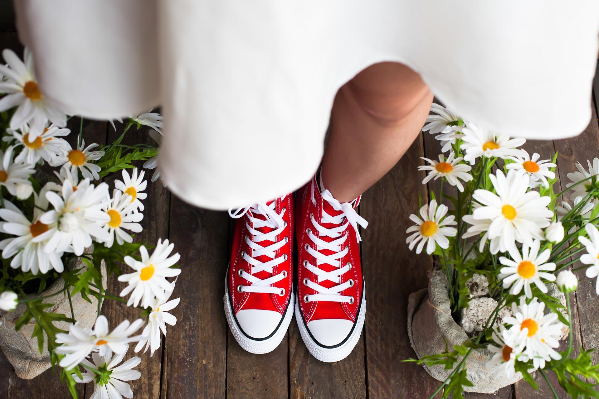 マリーゴールドの鼻が埋められた床に知りスカートと赤いコンバースの女性の足が立っている