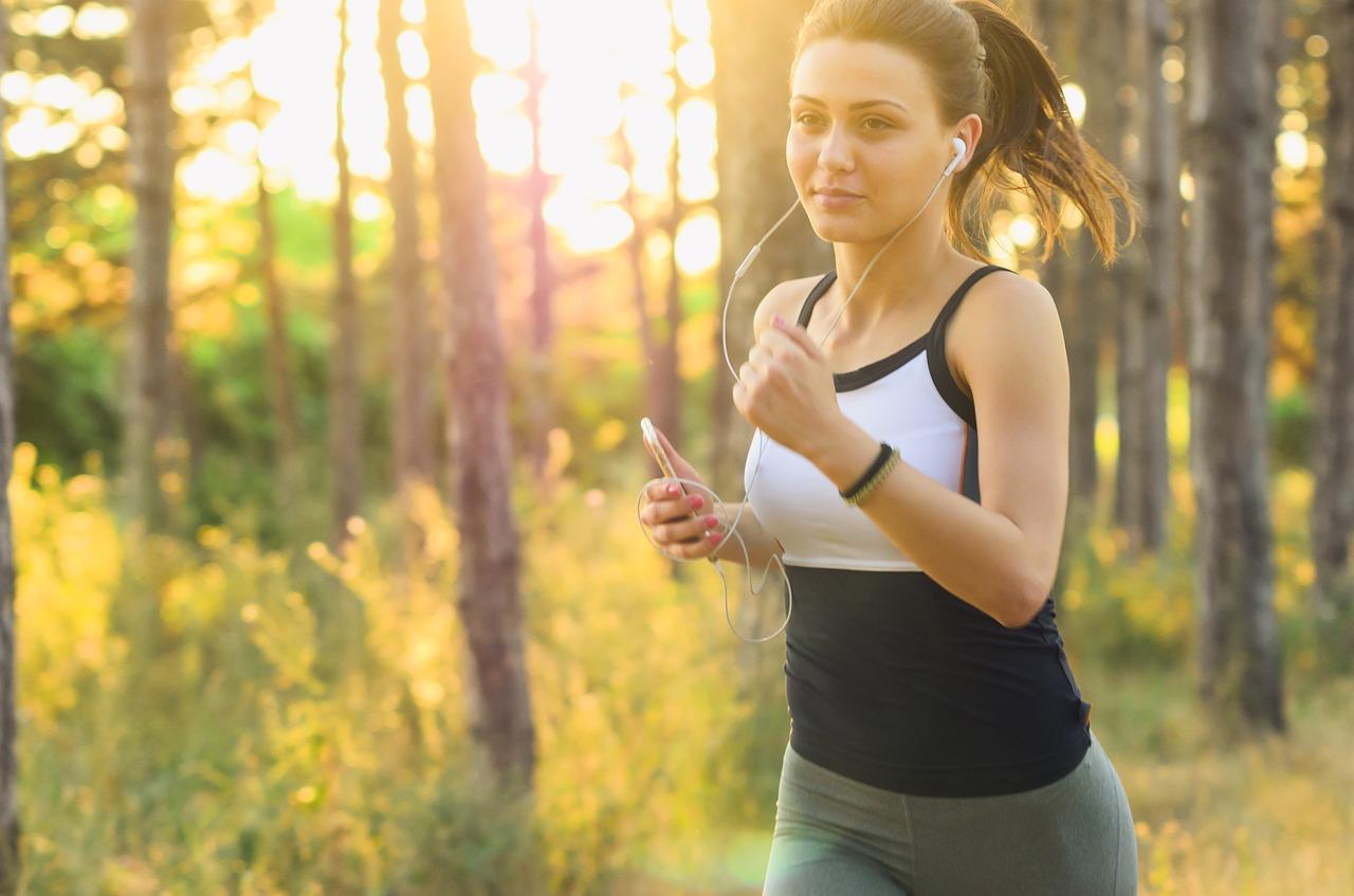 イヤホンで音楽を聴きながらジョギングする女性の写真