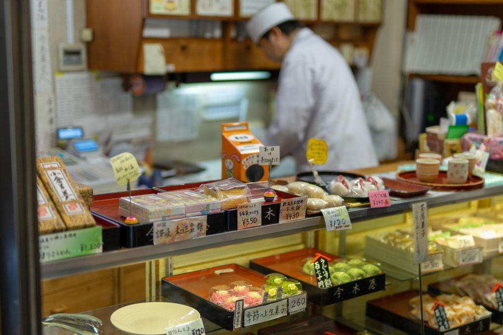 老舗和菓子屋「今木屋」の主人と店頭に並ぶ和菓子たち
