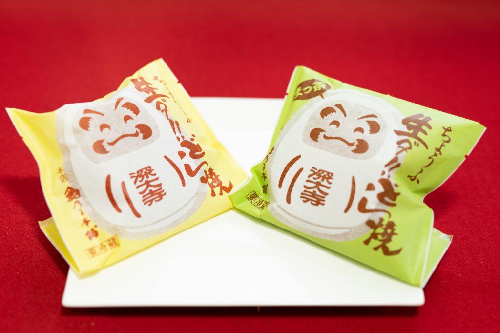 「亀乃子本舗」の名物「生ダ!どら焼き」のかわいいだるまが笑っているパッケージ。